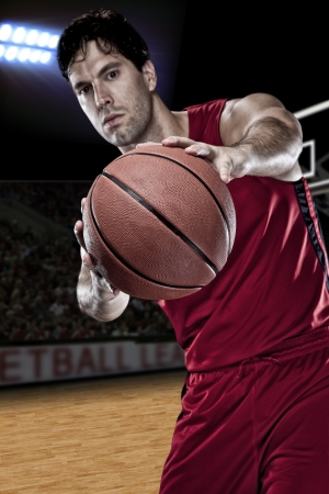 Basketball player with a ball in his hands and a red uniform. photography studio. photo