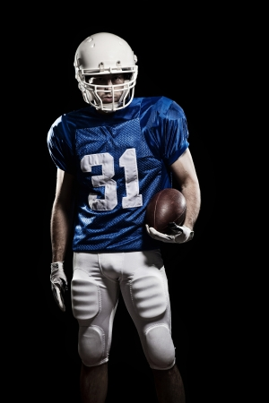 recreational sport: Football Player with number on a blue uniform and a ball in the hand. Studio shot.