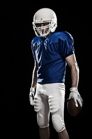 Football Player with number on a blue uniform and a ball in\ the hand. Studio shot.