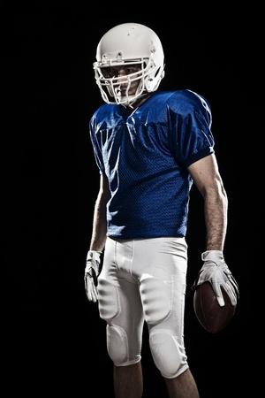 jugador de futbol americano: Jugador de f�tbol con el n�mero en el uniforme azul y una pelota en la mano. Estudio de disparo.