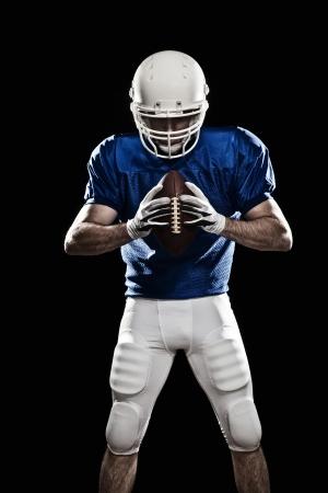 jugador de futbol: Jugador de f?tbol con el n?mero en el uniforme azul y una pelota en la mano. Estudio de disparo.