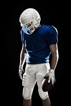 jugador de futbol: Jugador de f�tbol con el n�mero en el uniforme azul y una pelota en la mano. Estudio de disparo.