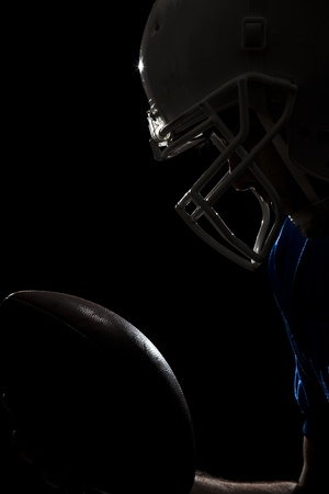 Football Player with number on a blue uniform and a ball in\ the hand Studio shot