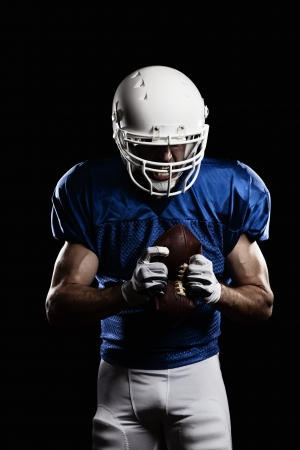 vertical wellness: Football Player with number on a blue uniform and a ball in the hand. Studio shot.