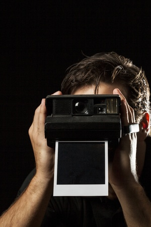 Photographer with a instant camera with a photography on black  photo