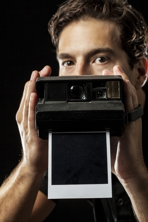 Photographer with a instant camera with a photography on black. photo