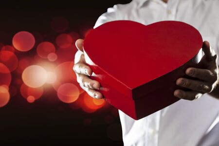 A Man holding a heart gift box in a gesture of giving  photo