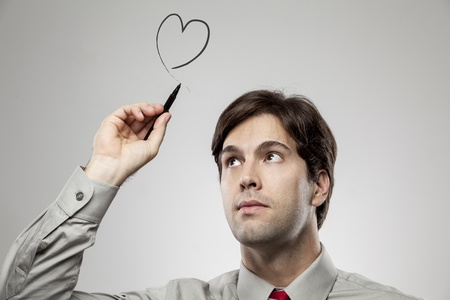 Man drawing a heart over his head, as if he is in love. photo