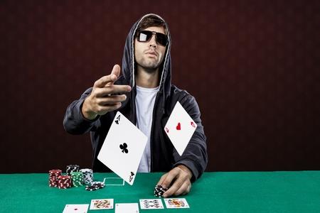 cartas de poker: Jugador de p�quer, sobre un fondo rojo, lanzando dos tarjetas as. Foto de archivo