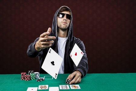 Poker player, on a red background, throwing two ace cards. Standard-Bild