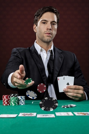Poker player, on a red background, throwing poker chips. photo