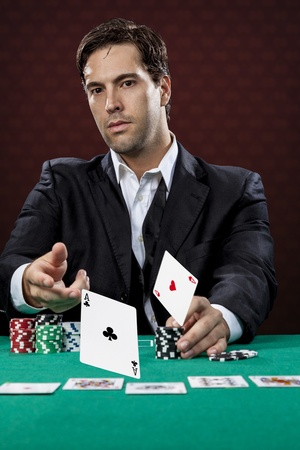 card player: Poker player, on a red background, throwing two ace cards. Stock Photo