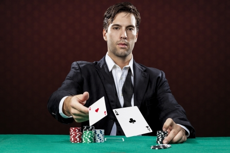 poker cards: Poker player, on a red background, throwing two ace cards. Stock Photo