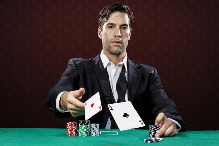 Poker-Spieler, auf einem roten Hintergrund, werfen zwei Ace Karten. Standard-Bild - 19900090