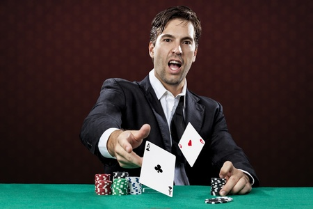 poker chips: Poker player, on a red background, throwing two ace cards. Stock Photo
