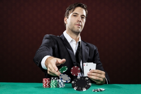 poker chips: Poker player, on a red background, throwing poker chips.