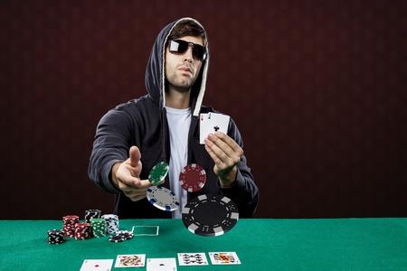 jetons poker: Joueur de poker, sur un fond rouge, jetant des jetons de poker. Banque d'images