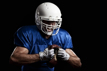 american football player: Football Player with number on a blue uniform and a ball in the hand. Studio shot.