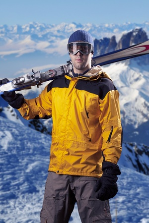 skier holding a pair of skis looking at the mountains. photo