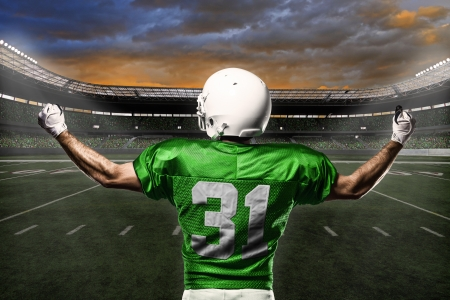 color fan: Football Player with a green uniform celebrating with the fans.
