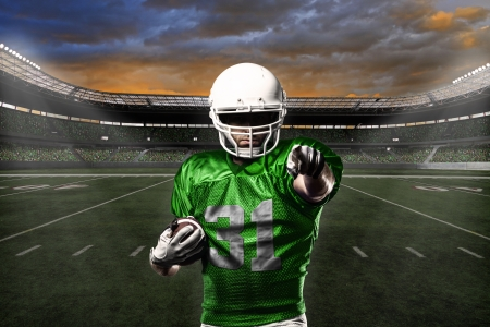american football player: Football Player with a green uniform celebrating with the fans.