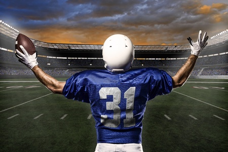 jugador de futbol: Jugador de f�tbol con un uniforme azul que celebra con los aficionados. Foto de archivo