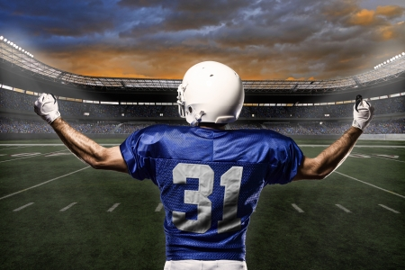 sports uniform: Football Player with a blue uniform celebrating with the fans.