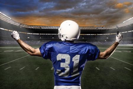 jugador de futbol americano: Jugador de f�tbol con un uniforme azul que celebra con los aficionados. Foto de archivo