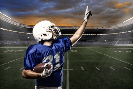 football fan: Football Player with a blue uniform celebrating with the fans.