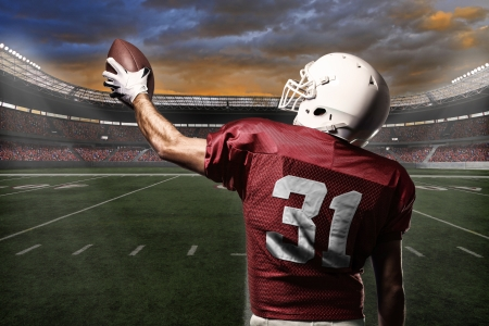 Football Player with a Red uniform celebrating with the fans. Stock Photo