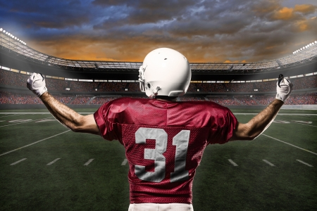 football: Football Player with a Red uniform celebrating with the fans. Stock Photo