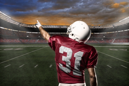 american football ball: Football Player with a Red uniform celebrating with the fans. Stock Photo