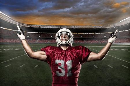 fútbol jugador: Jugador de f�tbol con un uniforme rojo de celebrar con los fans. Foto de archivo