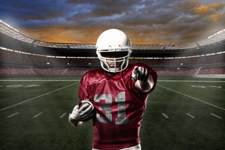 jugador de futbol: Jugador de f�tbol con un uniforme rojo que celebra con los aficionados. Foto de archivo