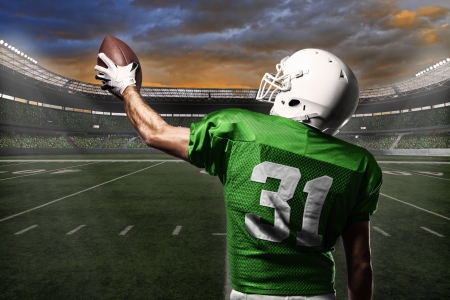 touchdown: Football Player with a green uniform celebrating with the fans.