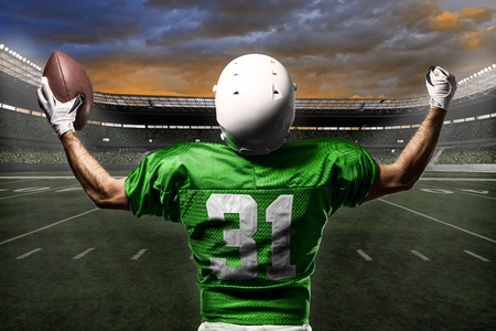 jugador de futbol: Jugador de f�tbol con un uniforme verde que celebra con los aficionados.