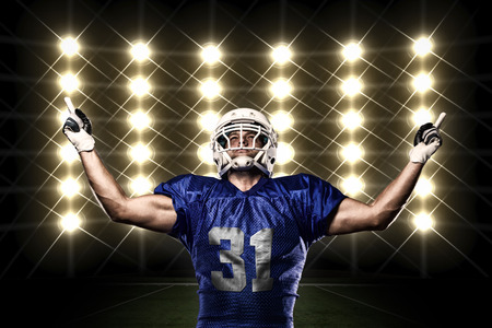futbolista: Jugador de fútbol con un uniforme azul de la celebración frente a las luces