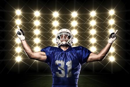 the football player: Jugador de f�tbol con un uniforme azul de la celebraci�n frente a las luces