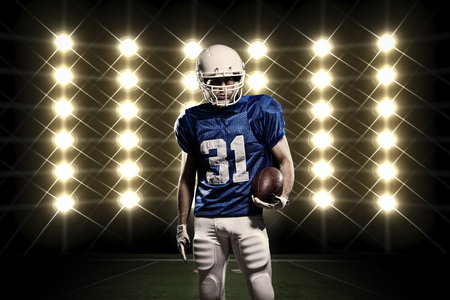 american football player: Football Player with a Blue uniform in front of lights