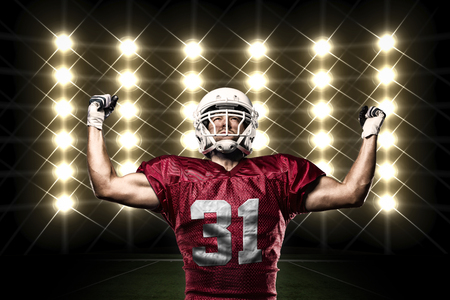 Football Player with a Red uniform celebrating in front of lights photo