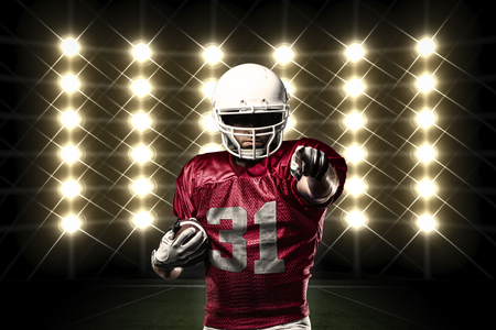 football player: Football Player with a Red uniform in front of lights.