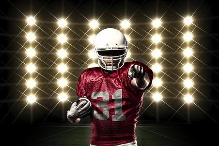 jugador de futbol americano: Jugador de f�tbol con un uniforme rojo delante de las luces. Foto de archivo