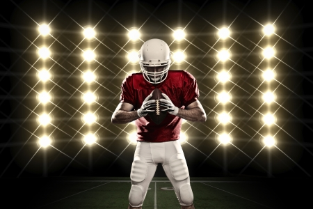 Football Player with a Red uniform in front of lights. photo