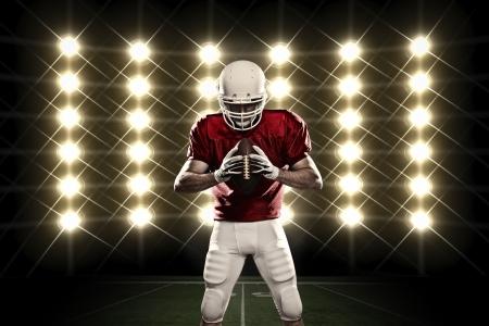 casco rojo: Jugador de f�tbol con un uniforme rojo delante de las luces. Foto de archivo