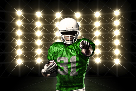 Football Player with a green uniform in front of lights. photo