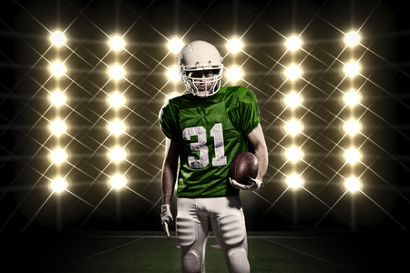 sports uniform: Football Player with a green uniform in front of lights.