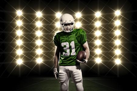 uniforme de futbol: Jugador de f�tbol con un uniforme verde delante de las luces.
