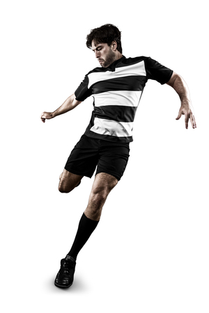 Soccer player in a black and white uniform kicking photo