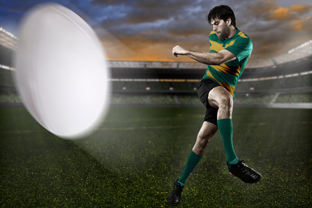 Rugby player in a green and gold uniform kicking Standard-Bild