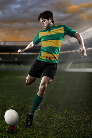 Rugby player in a green and gold uniform kicking photo